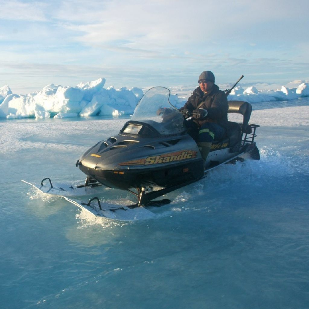 Inuit hunter travelling by skidoo on melting ice - © RÉMY MARION