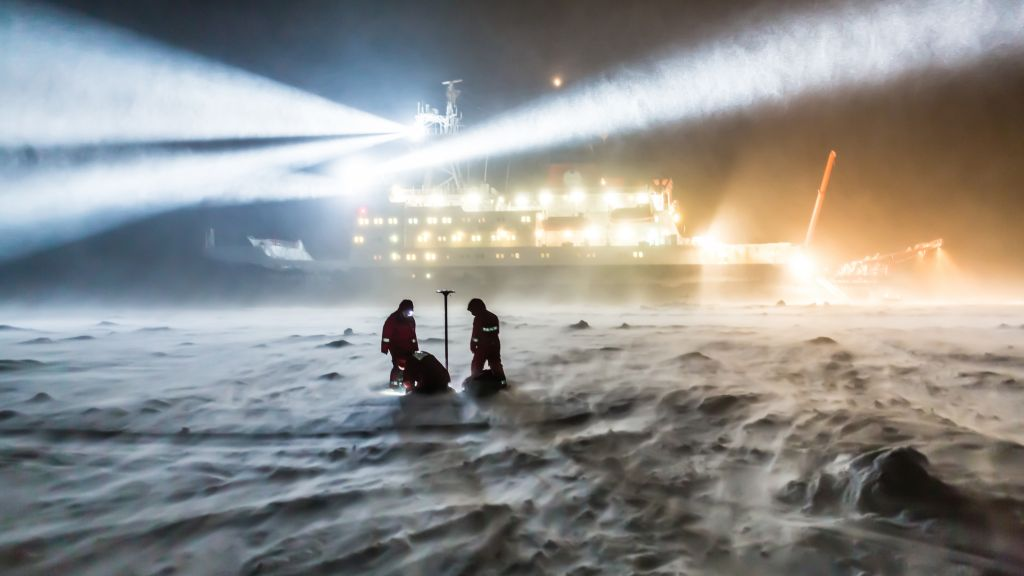AWI sea ice physicists taking measurements on the sea ice in the darkness of the polar night.