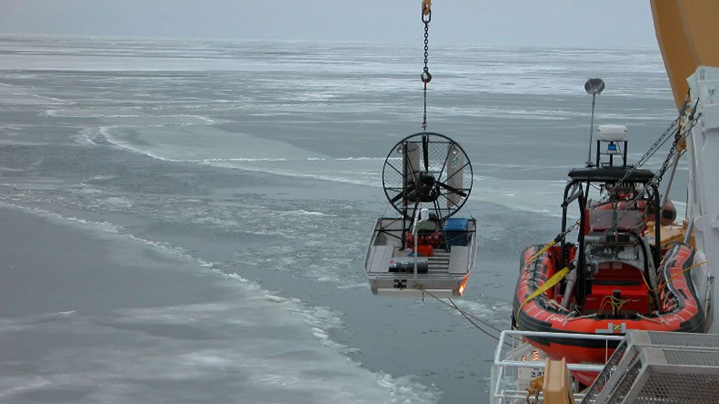 The Amundsen lowering a small boat into an area of thin sea ice in the Arctic Ocean