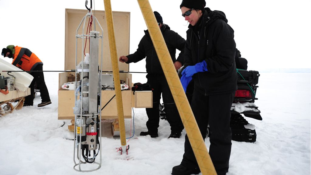 Katherine Leonard preparing to lower a CDT sensor beneath the ice shelf