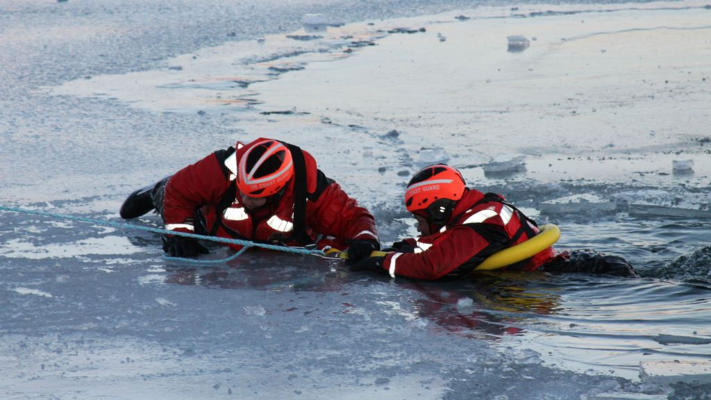 Members of the US Coast Guard stage a practice rescue in ice-covered waters.